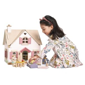 creative kid playing with a wooden dollhouse