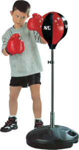 an active kid wearing boxing gloves standing in front of a punching bag